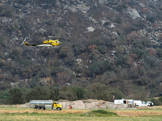 A helicopter lands in a refueling and loading area along Balch Park Road as the Pier Fire continues to burn above Springville on Wednesday, Sept. 6, 2017