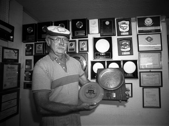 """Inventor Ed Headrick of Lakeport, Calif., holds a Frisbee and its prototype, a Mother Frisbie's pie tin, in this 1985, photo. Headrick, father of the modern Frisbee and designer of Wham-O's first """"professional model"""" flying disc, died in 2002."""