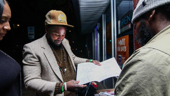 "Homeless Wilmington artist Davon Marque Hall, center, provides insight about his ""Black Lives Matter"" coloring books during the Wilmington Art Loop at Daily Bread convenience store on Nov. 4."
