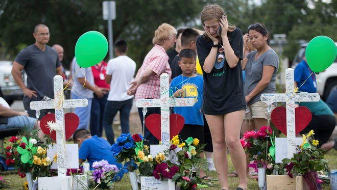 A girl becomes emotional at a makeshift memorial outside Santa Fe High School in Texas, May 22, 2018.