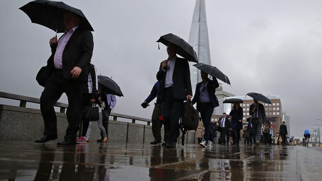 People cross the London Bridge heading into work Monday were greeted by continuing fallout from Britain's historic vote to exit the European Union. Standard & Poor's stripped the U.K. of its triple-A credit rating Monday, citing instability from the referendum's outcome.