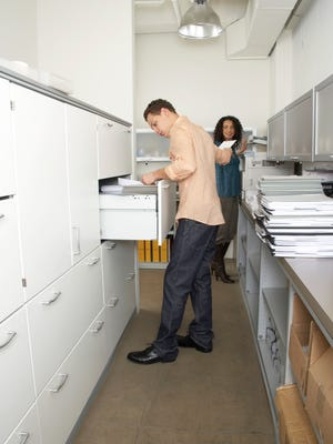 Businessman and businesswoman looking through files in office