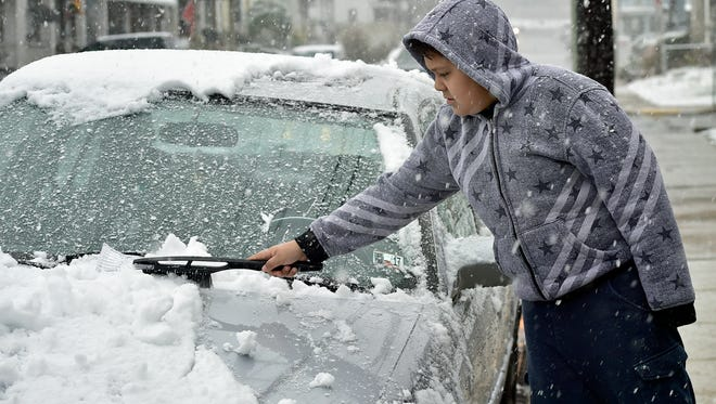 Eliel Soto, 10, brushes snow off his dad's car on Second Street during a morning snowfall in Chambersburg. Soto was getting the car ready so he could be transported to school on March 10, 2017.