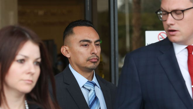 Former Coachella police officer Oscar Rodriguez, center, walks out of the Larson Justice Department in Indio, Jan. 3, 2018.  Rodriguez has been charged with murder.