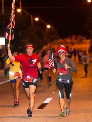 Brian Sumwalt carries the American and POW flags while running the annual Midpoint Madness Veterans Day 5K with his wife Pat Curr on Tuesday, November 11, 2014, in Fort Myers.