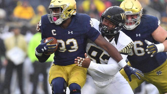 Fighting Irish running back Josh Adams (33) is hit by Wake Forest Demon Deacons defensive tackle Zeek Rodney (93) in the first quarter at Notre Dame Stadium.