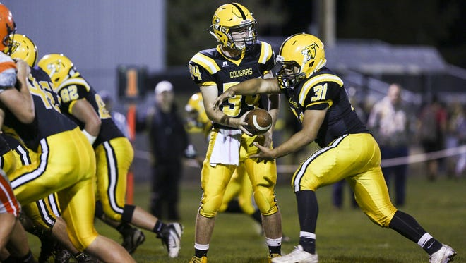 Cascade's Gavin Bettelyoun (34) hands the ball off to Marcos Reyes (31) in a game against Yamhill-Carlton on Friday, Sept. 23, 2016, at Cascade High School in Turner. The Cascade Cougars defeated Yamhill-Carlton 60-8.
