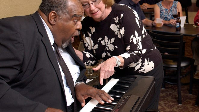 Al Martin reacts in surprise as Liz Richbourg tells him how her grandmother taught herself to play the number he is shown playing, The Entertainer, at age 90.  Martin has entertained generations of fans and piano students with this talent.  He is shown performing Friday night at the Quality Inn & Suites on Scenic Highway.