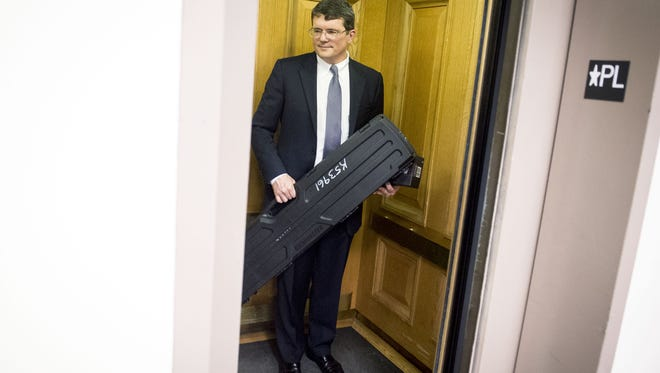 Rep. Mike Stewart, D-Nashville, boards an elevator with a case containing a rifle after speaking about purchasing the rifle without undergoing a background check, at Legislative Plaza, Wednesday, March 23, 2016, in Nashville, Tenn.