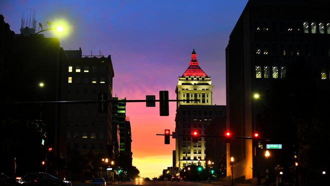 The sun sets behind the skyline of downtown Peoria on Wednesday evening as the lights of the city illuminate buildings on June 5, 2019.