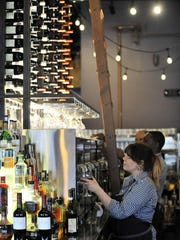 Sandria Haney pours a glass of wine from the elaborate collection at Pop's for Italian in Ferndale.