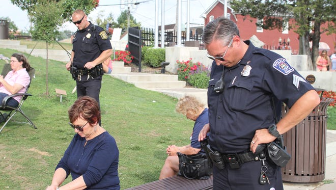 Residents and police pause for a moment of prayer Wednesday.