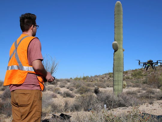 Ben Stinnett, a student in the Arizona State University robotics program and a quad-copter pilot, guides in his research drone for a smooth landing.