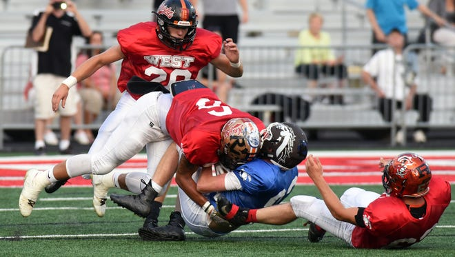 River View grad Keith Stewart lays a crushing hit on an East receiver during the West's 20-10 win in the Times Reporter Charities All-Star Game on Friday at Woody Hayes Quaker Stadium in New Philadelphia. Stewart was named Defensive MVP for the West.