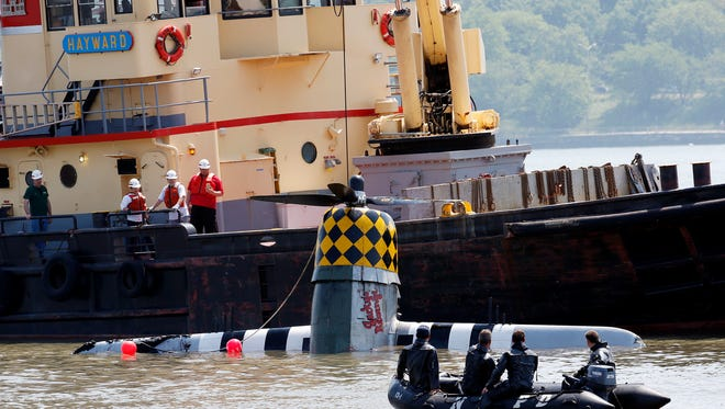 Officials remove a plane out of the Hudson River a day after it crashed, Saturday, May 28, 2016, in North Bergen, N.J. The World War II vintage P-47 Thunderbolt aircraft crashed into the river Friday, May 27.  (AP Photo/Julio Cortez)