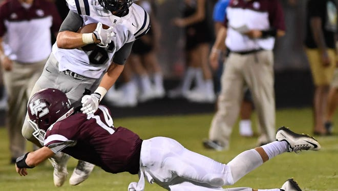 Reitz's Calvin Brinton is tackled by Henderson's Nate Sigler as the Henderson County Colonels host the Reitz Panthers for the Hall of Fame game at Colonel Stadium Friday. The matchup is the first game of the season for both teams, August 19, 2016. 6 14