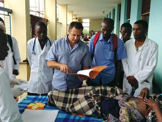 Dr. Joseph Fulton (center) goes over a patient's chart