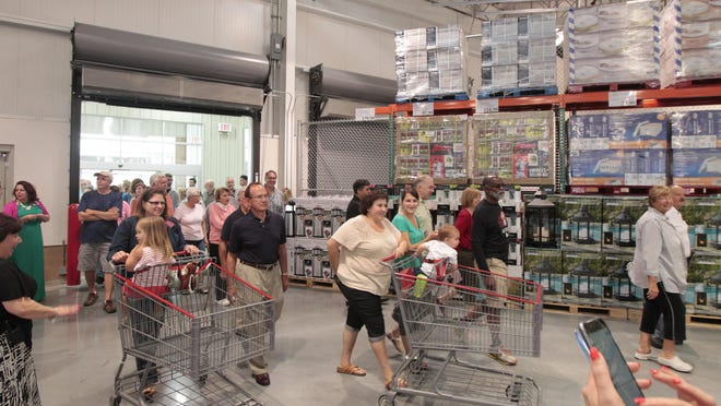 Hundreds flood through the main entrance at the Costco VIP opening held Thursday night at their new CityGate store on Westfall Avenue in Rochester. The store opens to the public on Friday morning.