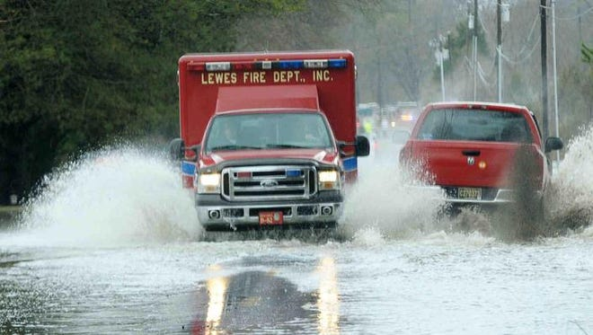 Lewes officials hired a consultant in hopes of improving its rating and lowering costs for residents on flood insurance. Emergency crews travel through a flooded King road in this 2010 photo.