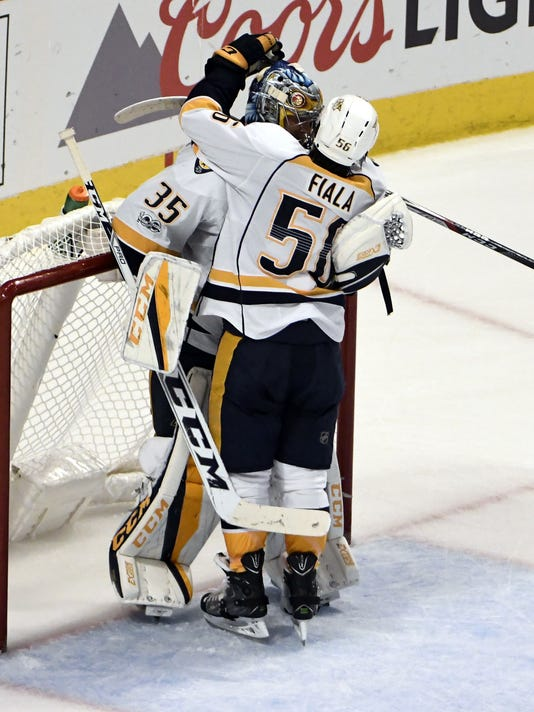 Nashville Predators goalie Pekka Rinne (35) and center Kevin Fiala (56) celebrate their win against the Chicago Blackhawks in Game 2 of a first-round NHL hockey playoff series, Saturday, April 15, 2017, in Chicago. The Predators won 5-0. (AP Photo/David Banks)
