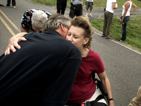 """Text: Amy Hawkins gets a hug from her father Robert Golden after she and her husband Jerrod, visited the site of their former home with a crew from """"Extreme Makeover: Home Edition."""""""