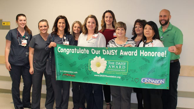 Rebecca Perkins, RN, poses with her coworkers and hospital leadership after being presented with the DAISY Award for Extraordinary Nurses.