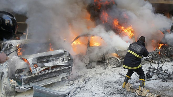 Lebanese firefighters extinguish fire from burning cars following an explosion on January 21, 2014 in Haret Hreik, a south Beirut neighbourhood considered a stronghold of the Lebanese Shiite movement Hezbollah. Two people were killed in the apparent suicide car bombing, Lebanon's National News Agency said. AFP PHOTO/STRSTR/AFP/Getty Images ORIG FILE ID: 526257536
