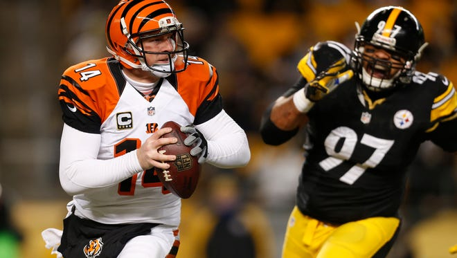 Bengals quarterback Andy Dalton is pursued by Steelers defensive end Cameron Heyward on Dec. 15, 2013.