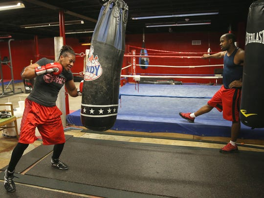 Cierra Taylor (L) works on the bag with trainer Derick Gramling  at World Gym on East Ave.  Taylor, a single mother of three, will fight in the USA Olympic Boxing  Trials in Memphis, Tennessee.