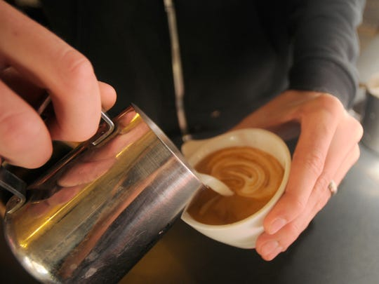 A barista at Mars Cafe whips up some latte art at the