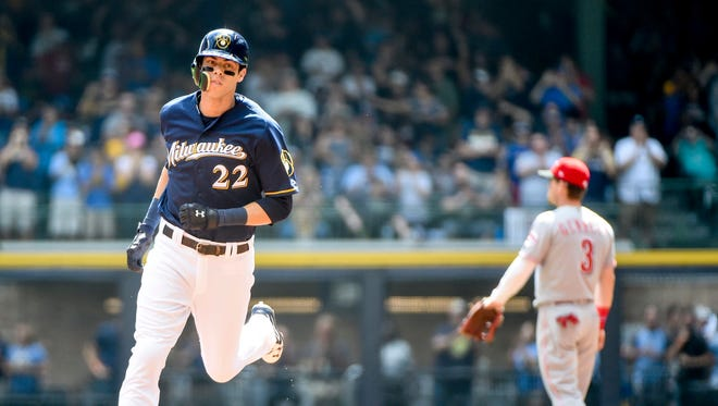 Milwaukee Brewers right fielder Christian Yelich (22) runs the bases after hitting a solo home run as Cincinnati Reds second baseman Scooter Gennett (3) watches in the first inning at Miller Park.