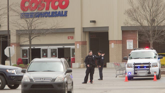 Green Oak Police officers, as well as Costco employees, divert incoming cars away from the parking lot in front of the Costco store on Whitmore Lake Road in Green Oak Township after reports of a bomb threat.