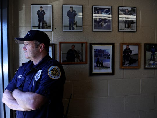 Metro police Officer Terry Burnett of the K9 unit stands near portraits of other officers and their police dogs.