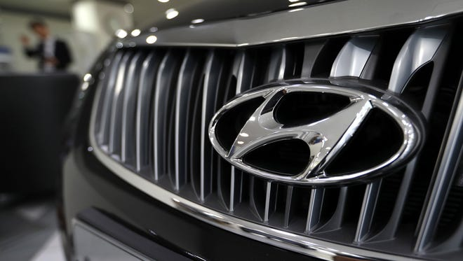 The logo of Hyundai Motor Co. is seen on a car displayed at the automaker's showroom in Seoul, South Korea, Wednesday, Oct. 26, 2016. Automakers Hyundai Motor Co. and Kia Motors Corp. will pay $41.2 million to 33 states and the District of Columbia to settle an investigation into their fuel economy ratings.