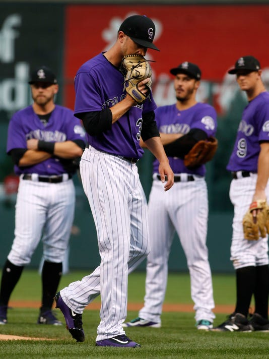 Colorado Rockies starting pitcher Kyle Freeland heads to the dugout as infielders watch after Freeland was injured while throwing a pitch to Philadelphia Phillies' Aaron Altherr during the first inning of a baseball game Friday, Aug. 4, 2017, in Denver. (AP Photo/David Zalubowski)