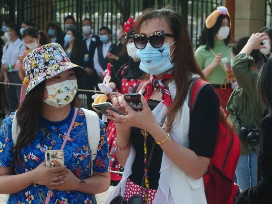Visitors, wearing face masks, wait at the entrance of the Disneyland theme park in Shanghai as it reopened Monday. Visits will be limited initially and must be booked in advance, and the company said it will increase cleaning and require social distancing in lines for the various attractions.