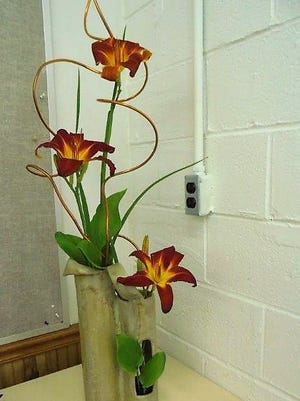 """This simple arrangement represented""""Music Class.""""It was made with copper tubing, tetraploid daylilies, and a few hosta leaves and entered in the Derby Garden Club's flower show."""