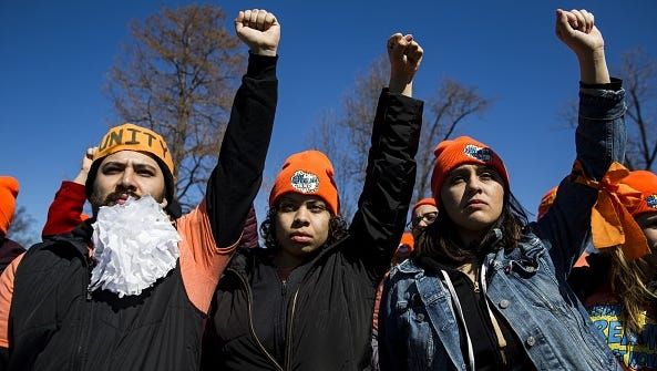 Demonstrators raise their fists in protest of President Trump's attempts to end the Deferred Action for Childhood Arrivals (DACA), an executive action made by President Obama that protected minors known as Dreamers who entered the country illegally from deportation, outside of the U.S. Capitol in Washington, USA on March 5, 2018.