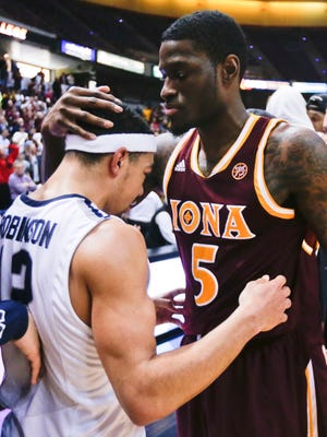 Iona guard A.J. English (5) embraces Monmouth guard Justin Robinson (12) after Iona's 79-76 win in an NCAA men's college basketball game in the championship of the Metro Atlantic Athletic Conference tournament on Monday, March 7, 2016, in Albany, N.Y. (AP Photo/Mike Groll)
