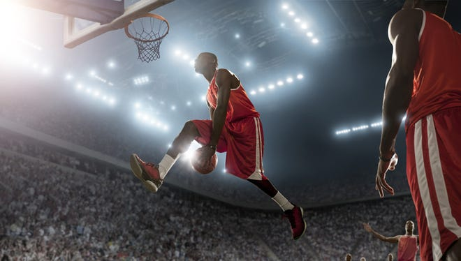 professional  basketball player jumping with ball about to score in indoor floodlit arena