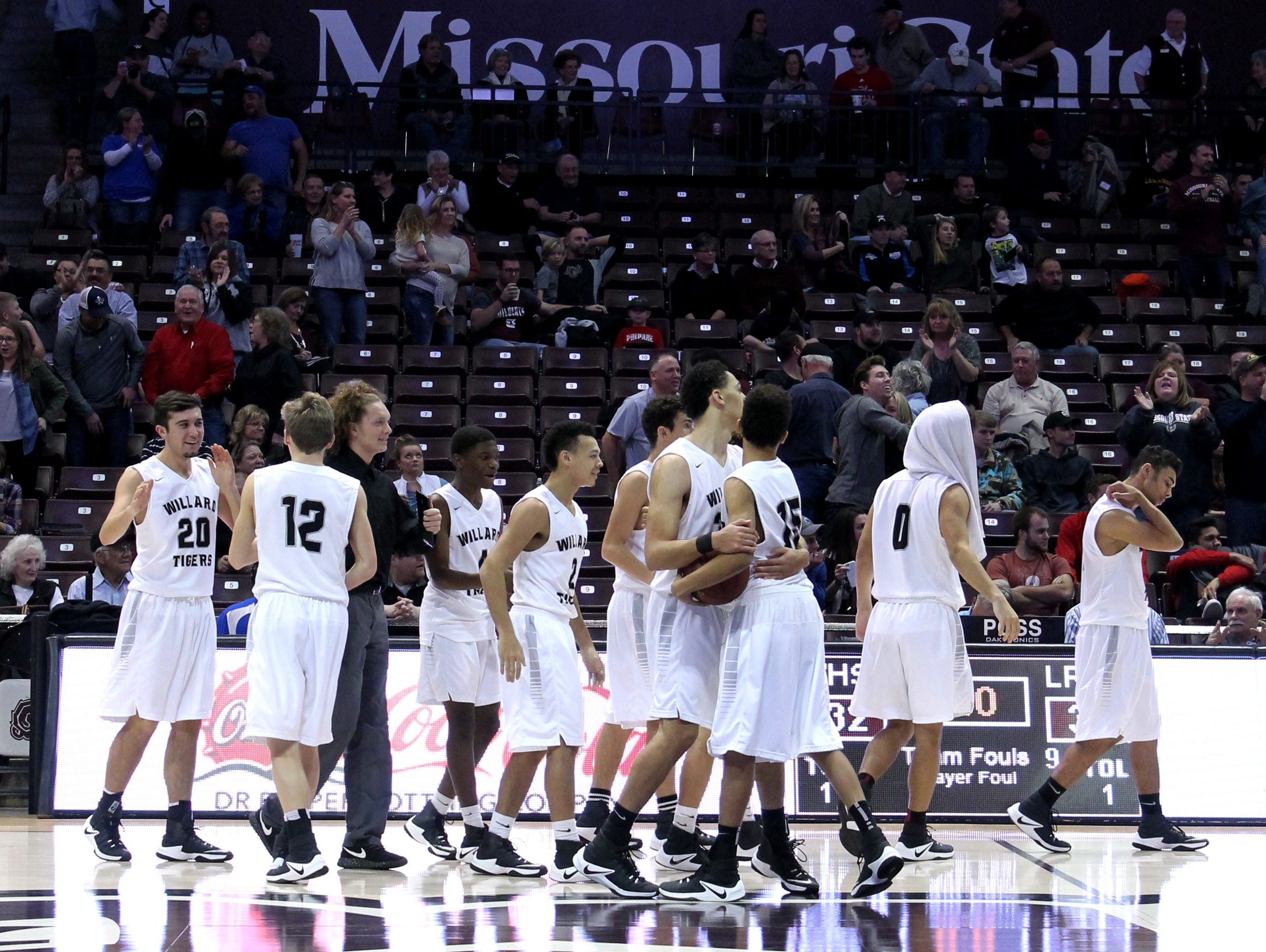 The Willard High School boys basketball team celebrates a 32-31 win over Rogersville in the Gold Division semifinals of the 71st annual Greenwood Blue and Gold Tournament at JQH Arena on Dec. 28, 2016.