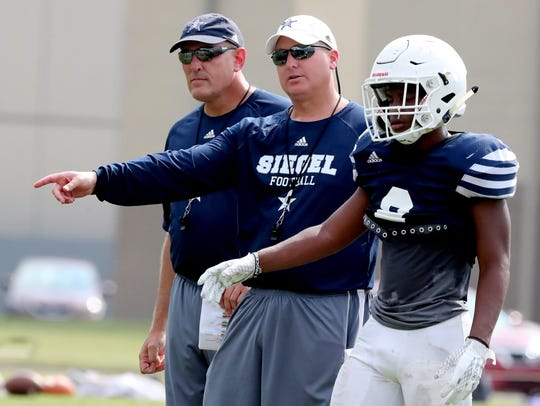 Siegel's head football Coach Michael Copley works with