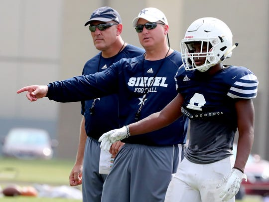 Siegel's head football Coach Michael Copley works with his players during a practice and a scrimmage against Father Ryan at Siegel High School, on Tuesday, July 31, 2018.