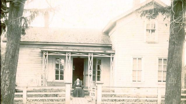Sally Paine Hack sits in front of her homestead at 14096 Plank Rd., Milan, perhaps around 1890.