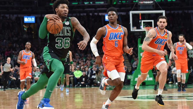 The Celtics' Marcus Smart, shown in a March 8 game against the Oklahoma City Thunder, tested positive for coronavirus but was asymptomatic. He and his teammates headed to Florida Wednesday to prepare for the resumption of the NBA season at the end of July.