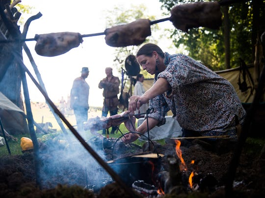 Elizabeth Huxford, of Oakland, Md., cooks food over a fire at the camp of Native American re-enactors during Mason and Dixon Day at the Mary Penn Bed and Breakfast on Saturday Aug. 20, 2016 near Gettysburg. The Southeastern Native Loyalist Confederacy was the re-enactor group portraying Native Americans. The event brings the history of the colonial time period and the French and Indian War to the Gettysburg area.