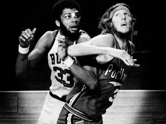 Bill Walton and Kareem Abdul-Jabbar battle for position in a game in 1975.
