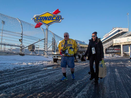 """Ross and Kim Page from Markham, Ontario leave the track at Martinsville Speedway in Martinsville, Va., Sunday, March 25, 2018. The NASCAR Cup Series race at Martinsville Speedway was postponed until Monday because of inclement weather. """"We're not leaving. We'll return tomorrow,"""" Ross said. (AP Photo/Matt Bell)"""
