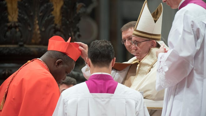 Archbishop of Bangui, Dieudonne Nzapalainga, left, kneels before Pope Francis to pledge allegiance and become cardinal, on Nov. 19, 2016 during a consistory at Peter's basilica. Pope Francis has named 17 new cardinals, 13 of them under age 80 and thus eligible to vote in a conclave to elect his successor.