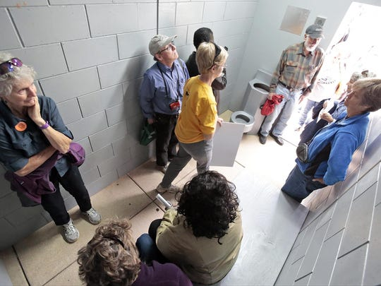 Attendees at a rally against solitary confinement spend time inside a mock solitary confinement cell outside the state Capitol in Madison in October. The cell, built by the statewide group Wisdom, is based in part on drawings made by former inmate Talib Akbar during one nearly yearlong stint in isolation.